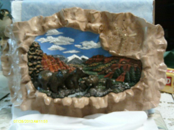 A 3D ceramic wall clock depicting a piece of buckskin with a scene of a red rock canyon in the back ground and Bears in the foreground on top of a ridge.