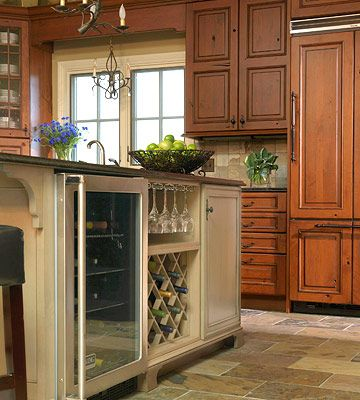 "Show Off Your Wine Storage:  ""Don't have the space for a separate wine bar? You can still showcase your collection by incorporating a wine bar into your kitchen island. This wine center includes a wine cooler for chilling bottles, a built-in rack, and slots for glasses. Just make sure to situate the wine center on the opposite side of the cooking area so it's easily accessible to guests."""