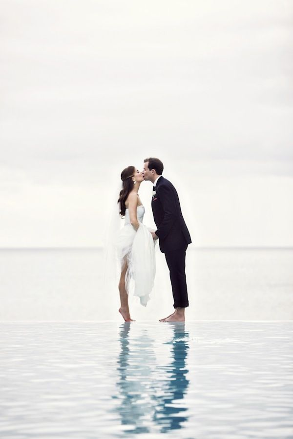 You may now kiss the bride! Stunning photograph of the bride and groom on the beach.