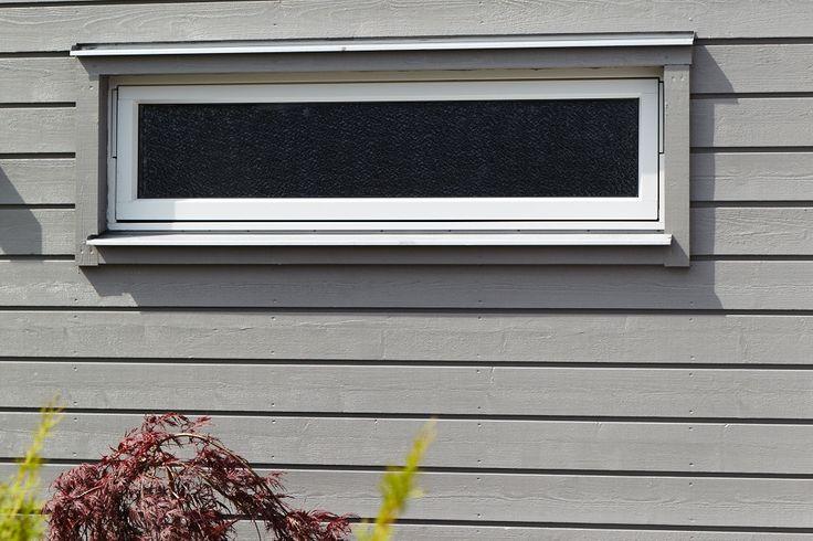 Detalj på liggande grå panel. Smala grå fönsterfoder. Trivselhus