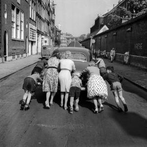 Kapotte auto wordt aangeduwd door vrouwen en kinderen, gemaakt door Dolf Kruger in de jaren '60 in de Nieuwe Kerkstraat in Amsterdam. Amsterdam (1958)