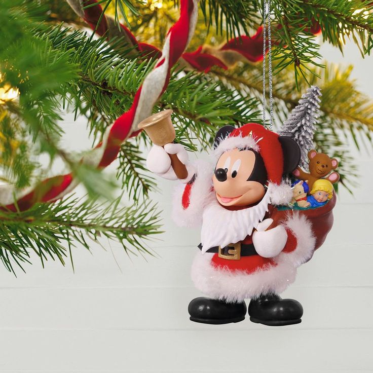Mickey is all dressed up in a Santa Claus suit with fake beard and fuzzy trim on this Christmas ornament. He also holds a bell and carries a bag full of toys.