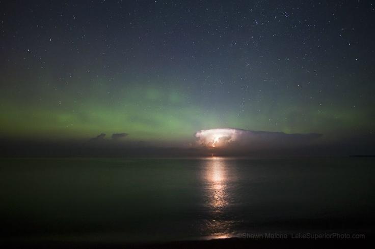 Una bellísima imagen de un cielo estrellado, auroras boreales y una tormenta eléctrica.