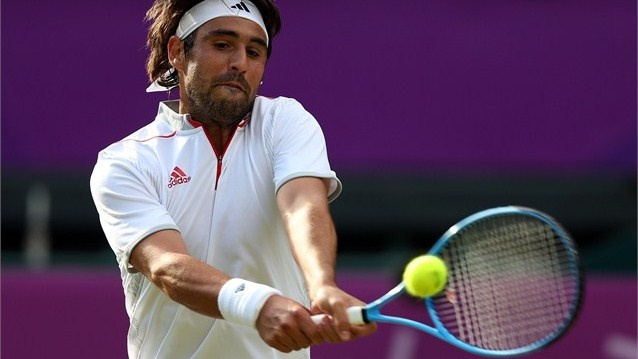 Marcos Baghdatis of Cyprus returns the ball to Andy Murray of Great Britain during the third round of Men's Singles Tennis on Day 5 of the London 2012 Olympic Games at Wimbledon.