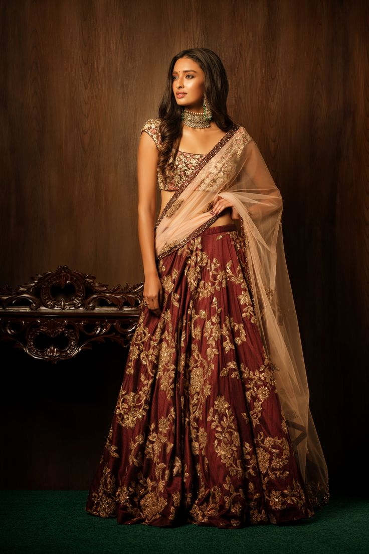 A stylish and stunning brownstone raw silk bias cut lehenga with a bold antique peeta jal, is teamed with a matching blouse ornamented with resham thread embroidery and a generous spray of sequins and pipes. The accompanying pale peach tulle dupatta has zardosi buttas and an encrusted border. The lehenga is easy to carry and elegant, and can be worn at an array of wedding functions like sangeet or mehendi. #bridal #trends #bridal2017 #bridalfashion #bridaldress #weddinglehenga