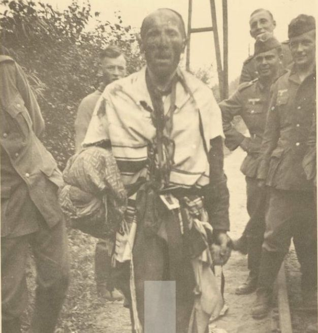 A Jew is surrounded by men of Einsatzgruppen A who have just shaved his beard and smeared his face with dirt.  And, the Germans smirk for the camera, as if this human being were of no more account than a pesky fly.  Once in the company of an Einsatzgruppe (mobile killing squads), there can be little doubt of a Jew's ultimate fate.