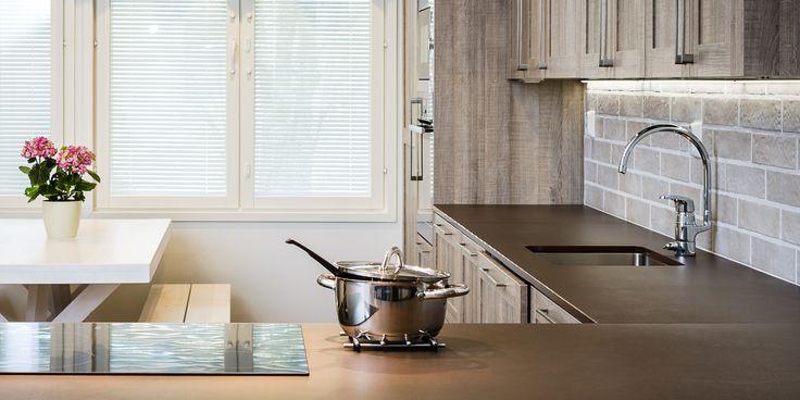 Puun pinta saa näkyä tunnelmallisessa keittiössä. Tiilikuvioitu tehosteseinä tuo lisää eloa ja kontrastia keittiöön.