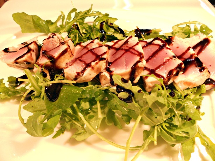 Tuna fillet on a rucola bed and flavored with balsamic vinegar reduction