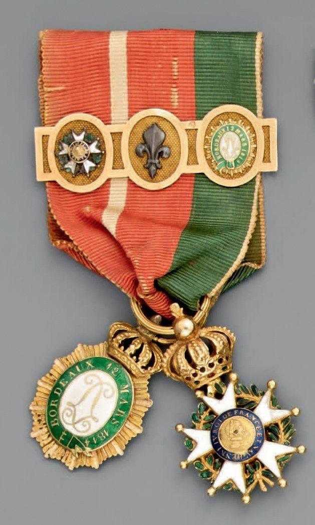 Deux réductions en or, émaillées, présentées avec ruban triple: une croix d'officier de l'ordre de la Légion d'honneur, quatrième type modifié Restauration; diamètre 23 mm et un insigne du Brassard de… - Maigret (Thierry de) - 08/11/2013
