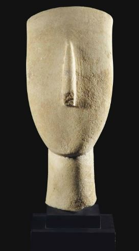 Cycladic marble head, late Spedos type, Early Cycladic II, 2500-2400 B.C. From a large reclining figure, sculpted with a lyre shaped head, chin rounded, the long triangular nose well centered, the neck flaring slightly and off set from the head by a shallow groove, 15.9 cm high. Private collection