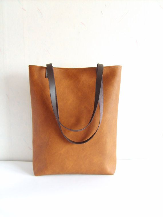Large vegan leather tote - cognac brown vegan/faux leather everyday tote bag. * Exterior: - High quality vegan/faux leather in gorgeous cognac brown color  * Interior: - Available with natural cotton polka dot lining in sandy beige and white or natural linen geometric print pattern in light beige. Please choose the lining you prefer from Variations. * Two inside slip pockets * Real leather handles in dark chocolate brown attached with antique toned brass rivets * Closes with magneti...