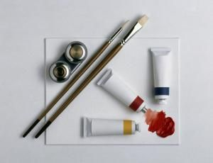 Learn How to Begin Oil Painting on Canvas: Artist's equipment of two brushes, three tubes of oil paint, and a metal dipper
