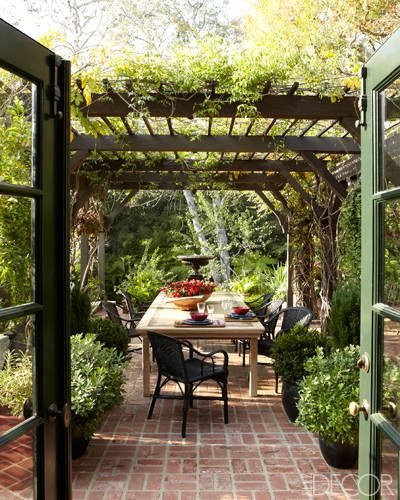 Chairs from Maison Midi surround an elm dining table beneath the pergola.