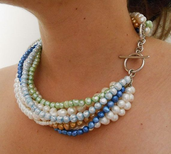A statement necklace with real pearls!    White , Light Green ,Blue, Bronze and Light Blue are the color of pearls ,the clasp is handmade and made by silver 925.The pearls are in different sizes.  The size of the necklace is close to the neck ,but it takes customization ,if you request it..Only one is available.