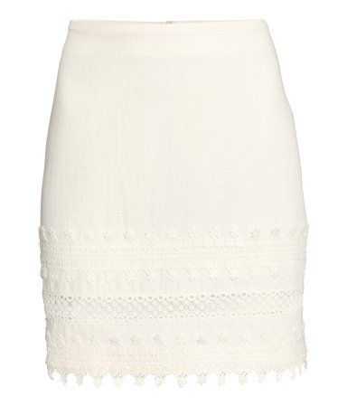 Short, fitted skirt in textured woven fabric. Wide, decorative lace trim at hem and concealed zip at back. Unlined.