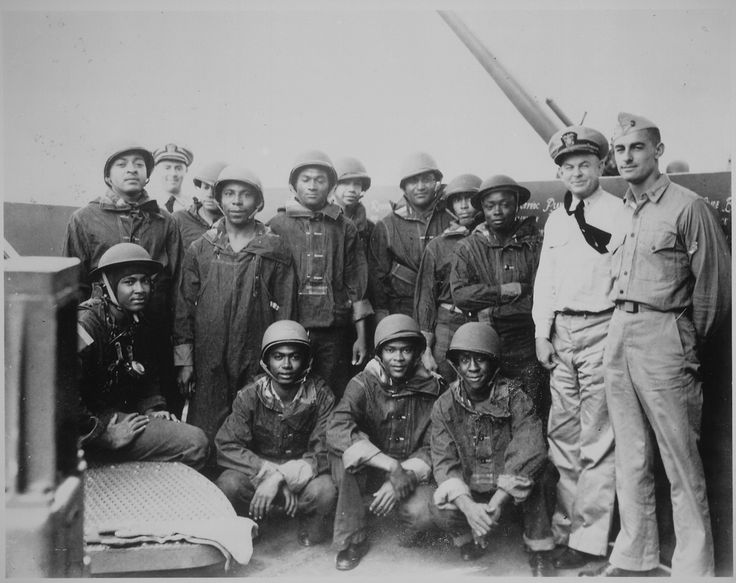 """""""Negro messmen aboard cruiser USS Indianapolis who volunteered for additional duty as gunners. They have been doing proficient work under battle conditions on a task force in the Pacific under the instruction of the officers at the right."""" 7/10/1942 (US National Archives)"""