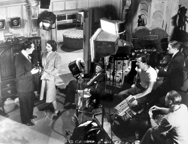 The filming of a scene from The Doctor Takes a Wife featuring Reginald Gardiner and Loretta Young. Director Alexander Hall is seated next to them, and cinematographer Sid Hickox is standing behind the camera 1941