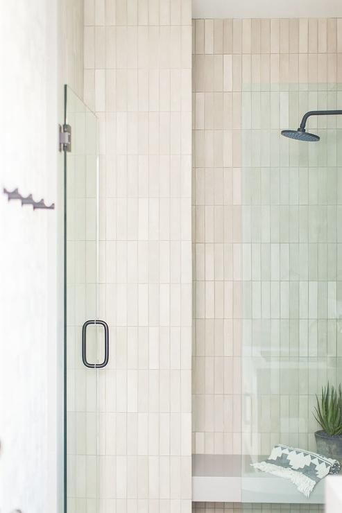 A seamless glass door opens to an outdoor walk-in shower clad in