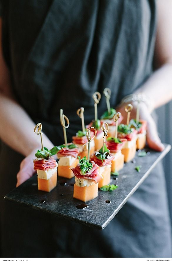 Cocktail hour food - melon, blue cheese, prosciutto & basil canapés.