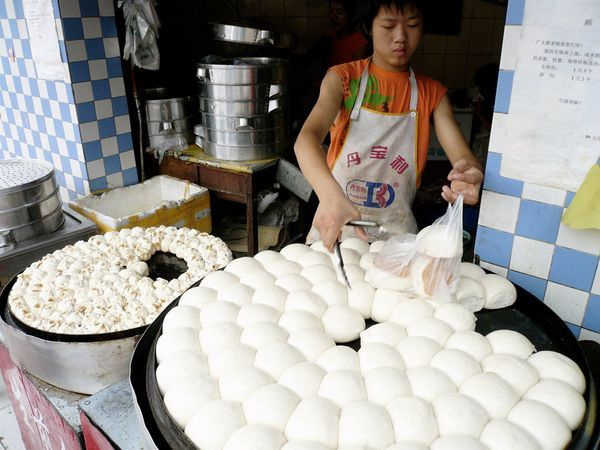 Breakfast in Chengdu - Though China is more commonly known for its rice products, large wheat crops in the north provide plenty of flour for local bakers. Steamed buns stuffed with meat or vegetables, known as baozi, are a popular breakfast on the go. - photograph by Greg Tillman