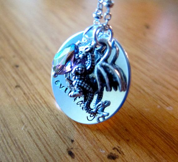 """Im a huge mouse fan and was inspired to create a line of necklaces inspired by some of my favorites movies. This was inspired by Sleeping Beauty and the evil fairy Maleficent. This necklace has a shiny silver colored charm, which has been hand stamped with """"evil fairy"""", as well as a"""