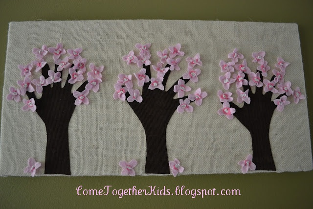 Kids handprint tree art for Mother's Day...thinking similar but instead of pre-cut flowers, use the eraser end of a pencil dipped in paint to create flowers/leaves..