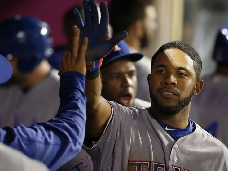 Texas Rangers' Elvis Andrus is congratulated in the dugout after scoring on a double by Bryan Holaday during the seventh inning of a baseball game against the Los Angeles Angels in Anaheim, Calif., Saturday, April 9, 2016. (AP Photo/Christine Cotter)