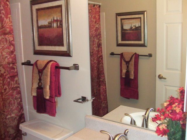 Bathrooms with white walls and red and tan towels for Staging bathroom ideas