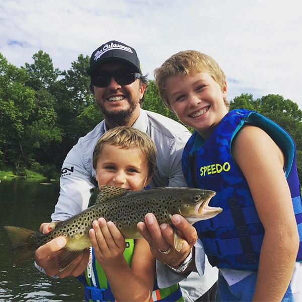 """""""HFE,"""" the country singer captioned a photo of himself and his two sons proudly holding up a fish they caught..."""