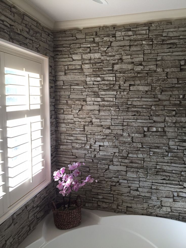 Gorgeous bathtub wall surround created with Norwich Stacked Stone panels in a light gray color.