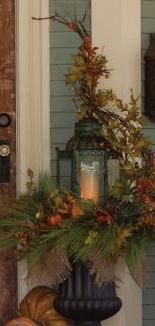 Lantern and greens in an urn with a burlap bow. Change the theme for all holidays!
