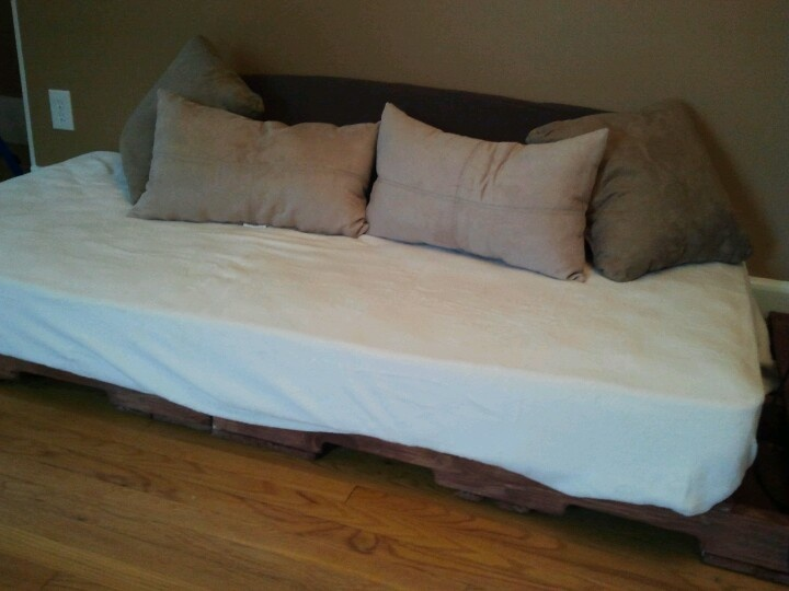 Repurposed wood pallets and twin mattress made into a couch.