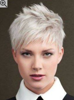 Feminine pixie cut with choppy side bangs and layers. The hair color is a very light blonde.