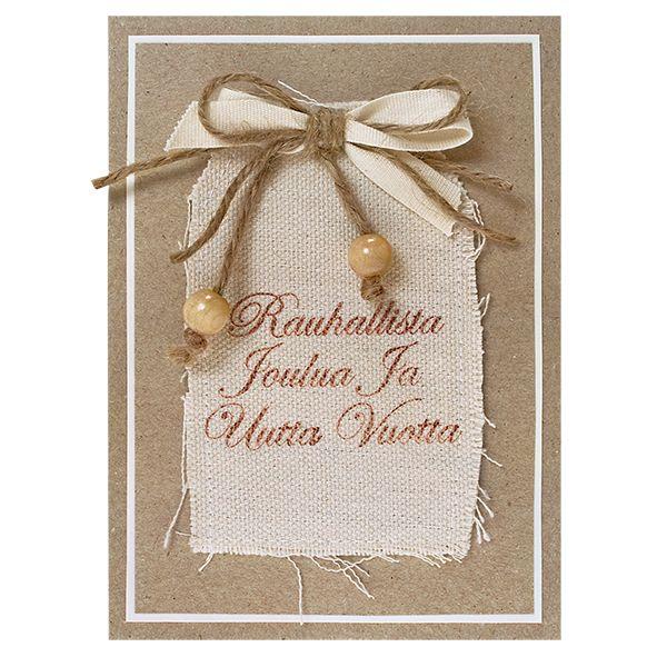 Kiinnitä akryylileimasin akryylipohjaan. Leimaile jouluntoivotus ruskealla versacraft-musteella valmiiseen kangastagiin. Leikkaa ekokartongista sopivan kokoinen suorakaiteen muotoinen pala, kehystä se luonnonvalkoisella Stucco-paperilla ja kiinnitä korttipohjaan. Kiinnitä tagi korttipohjaan kaksipuolisen voimateipin avulla. Tee puuvillanauhasta ja hamppunarusta rusetti, koristele hamppunarun päät puuhelmillä ja kiinnitä rusetti korttipohjaan.