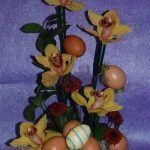 Arranjo floral Páscoa em base de espuma floral com Orquideas, margaridas e verdes num ninho de sisal. Decorado com ovinhos