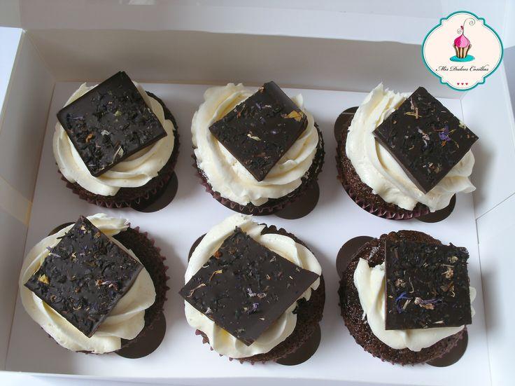 cupcakes de chocolate blanco con un trozo de chocolate negro al te negro y pétalos de flores