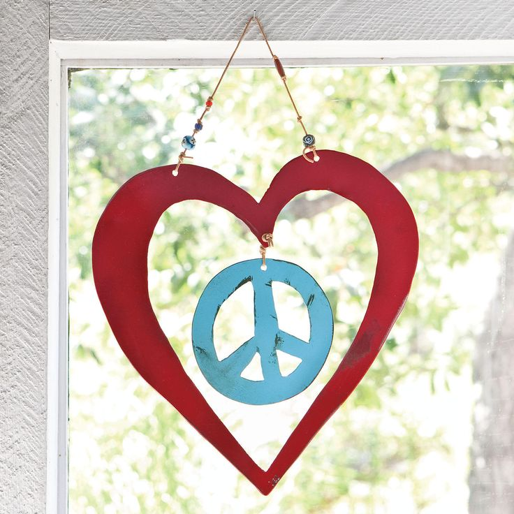 """PEACE WITH LOVE--Handmade by artist Jes MaHarry and her husband Patrick Henderson, this work of """"heart"""" welcomes all who enter your home with a message of love and peace. Handcut, handpainted steel hangs from leather cords strung with colorful trade beads. Signed by the artists and made in the USA. Approx. 10""""W x 11""""H."""