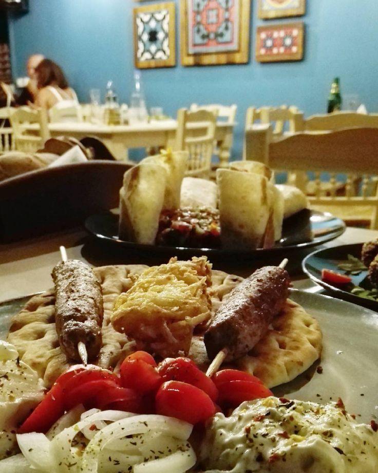 Un paese fuori dalle rotte turistiche un ristorante defilato una terrazza fuori dal tempo: a destra una parete azzurra con dipinti su legno a sinistra e sopra di noi un grande ficus. Sulla tavola cibi deliziosi: #kebab al piatto per lui con nidi di #patate #tsatziki e salsa #yogurt #roll vegetali per lei #livas #pitsidias #creta #creteisland #grecia #greece #greecestagram #greek #greekislands #happy #hellas #holiday #holidays #ig_greece #ig_crete #inlove #instacrete #island #love #paradise…