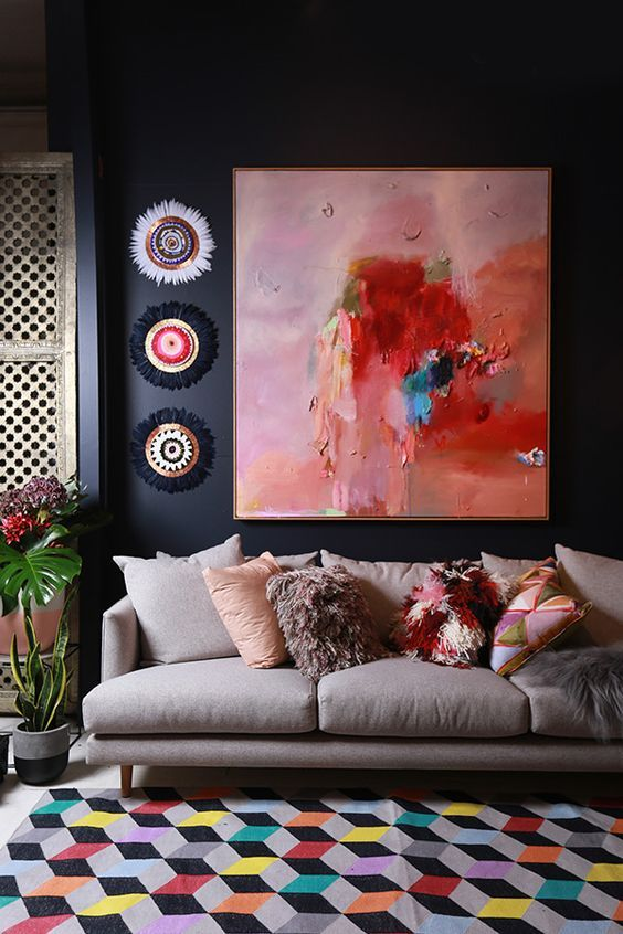 living room // dark walls // large abstract artwork // light gray sofa // geometric colorful rug // colorful throw pillows
