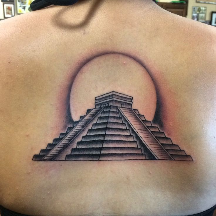 Tattoo of the Mayan pyramid El Castillo with a moon rising behind it