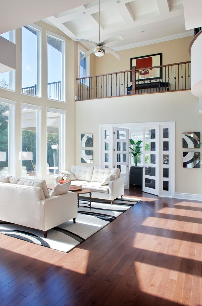 Soaring ceiling in this living room accommodates two story windows and an upper floor balcony overlooking the space. Twin white contemporary sofas are paired over black and white rug with two-tiered wood coffee table, with an expanse of rich hardwood flooring.