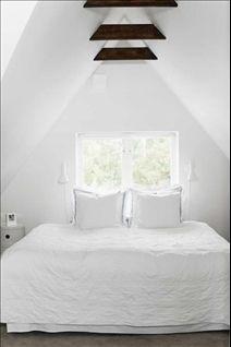 Sängkammaren i takkupan är helvit, alltifrån sängkläder och kuddar till sänglamporna från Nordiska galleriet.