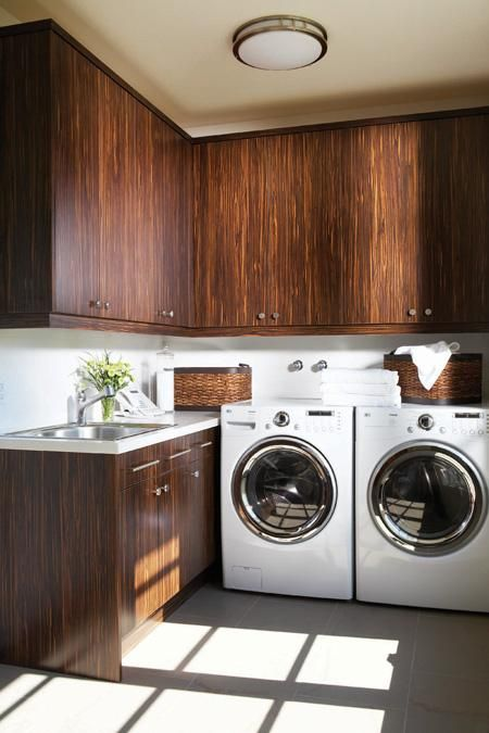 modern laundry room design with espresso wood cabinets, baskets, sink, gray slate tiles floors and white washer and dryer in modern laundry room.