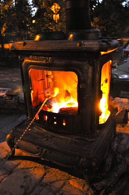 Use a salvaged wood stove for a fire pit. The fire heats the iron too for lasting warmth in the evening.