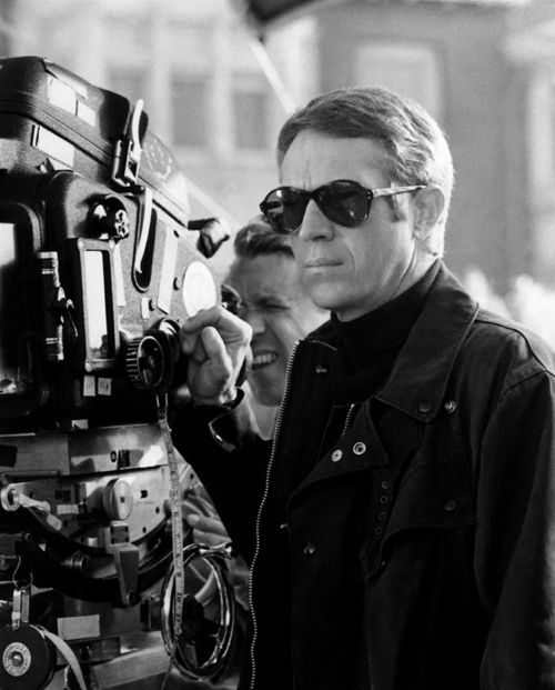 Steve McQueen on set and ready for action wearing some really cool aviator sunglasses!
