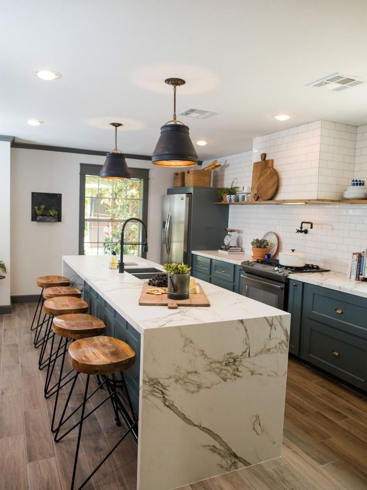 The kitchen of the newly renovated Jones home has been completely transformed. A wall was removed to increase the size of the kitchen and to add to the open feel of the home. Some key elements are the stainless steel appliances, farm sink, pantry, and subway inspired tile on the backsplash, as seen on Fixer Upper. (after)