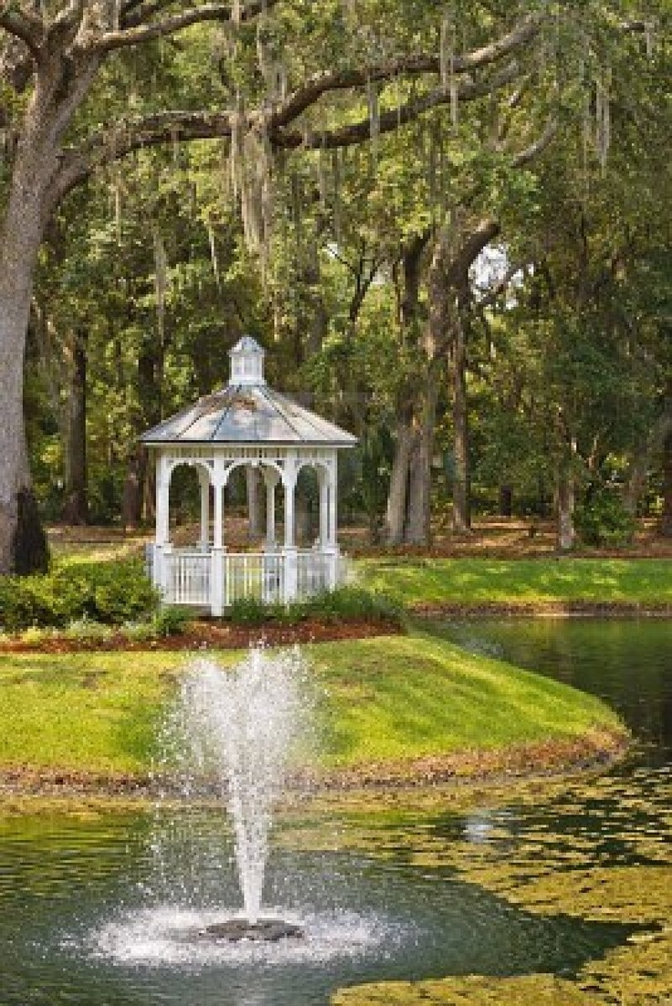 Holland park garden gallery brings in annuals from across ontario to - A White Wood Gazebo In The Woods With A Fountain In A Lake Stock Photo