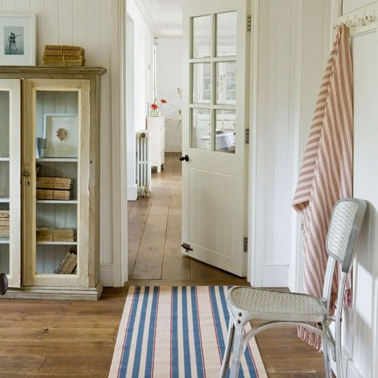 For a nautical decorating idea, try using a classic palette of red, white and blue. Painted tongue-and-groove panelling and natural wooden floorboards create a laid-back boathouse look, complemented by the striped rug
