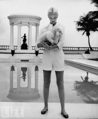 CZ Guest and her poodle standing by her Palm Beach swimming pool | Getty images
