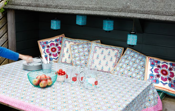 Patterned tablecloth and pillows with hanging lanterns, wire fruit bowl and retro tableware, all Carolyn Donnelly eclectic